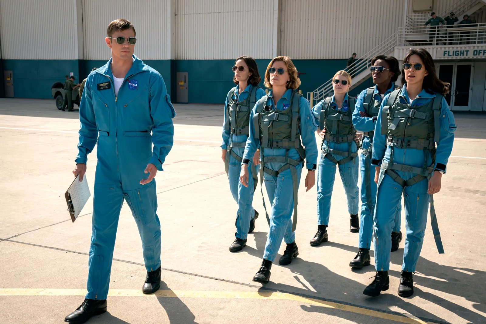 A male astronaut leads a cohort of female astronaut candidates onto the airfield. All wear aviators and have period-inappropriate hair.